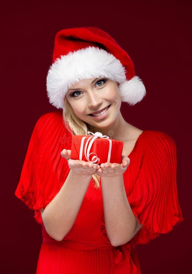 Den attraktiva flickan i jul cap händer en present royaltyfria foton