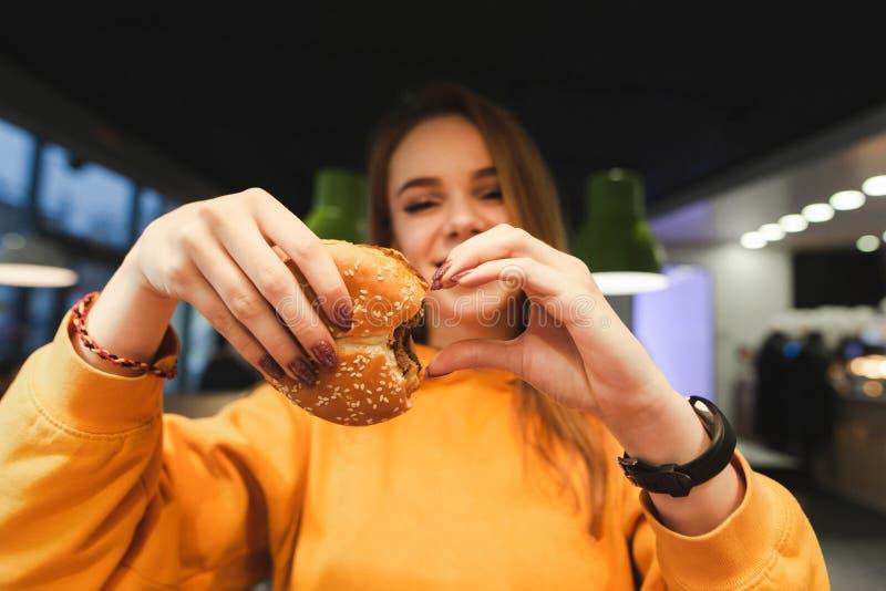 Den attraktiva flickan i orange bekläda håll i handen en stor smaklig hamburgare och visar ett tecken av hjärtan royaltyfria bilder