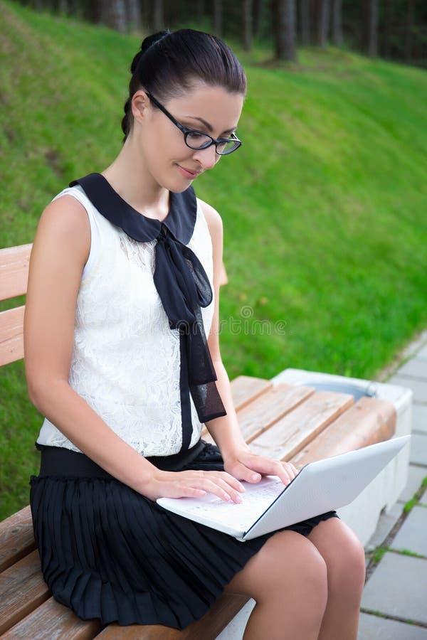 Den attraktiva flickan i skolalikformign som använder bärbara datorn parkerar in, eller universitetsområdet royaltyfria bilder
