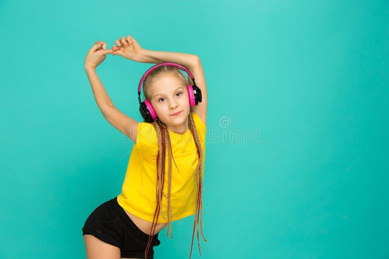 Den attraktiva flickan med hörlurar på blå bakgrund arkivfoton