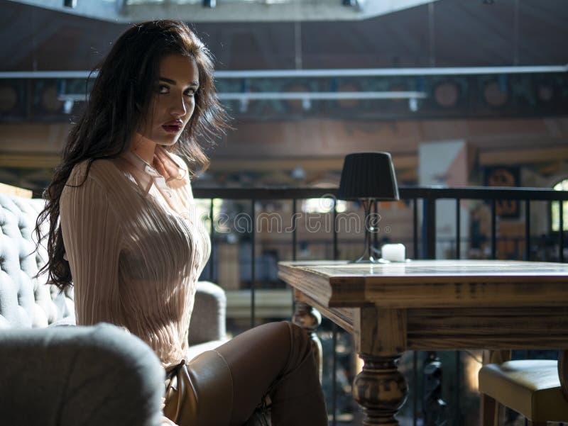 Den attraktiva flickan med lockigt hår och långa ben i en kort kjol sitter på soffan på tabellen royaltyfri fotografi