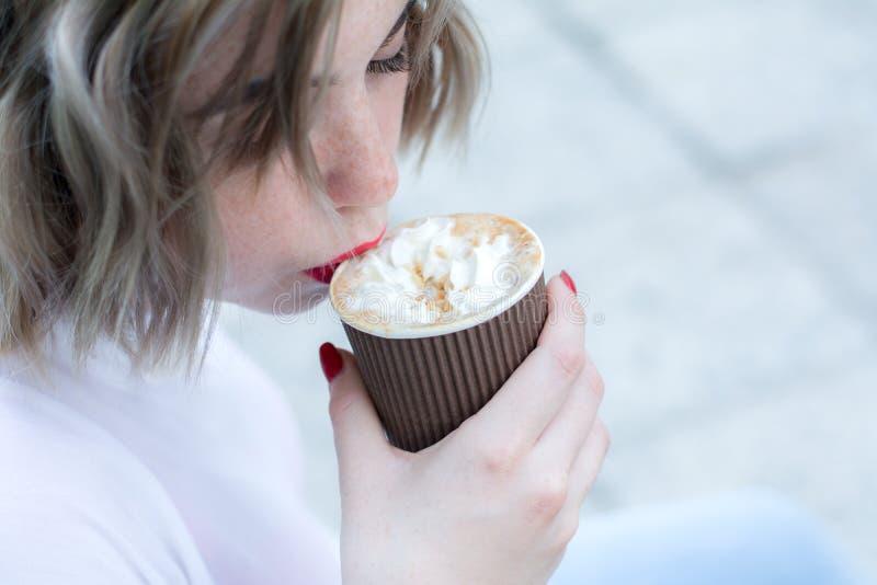Den attraktiva flickan med röda kanter tar en smutt av kaffe från den pappers- koppen arkivfoto