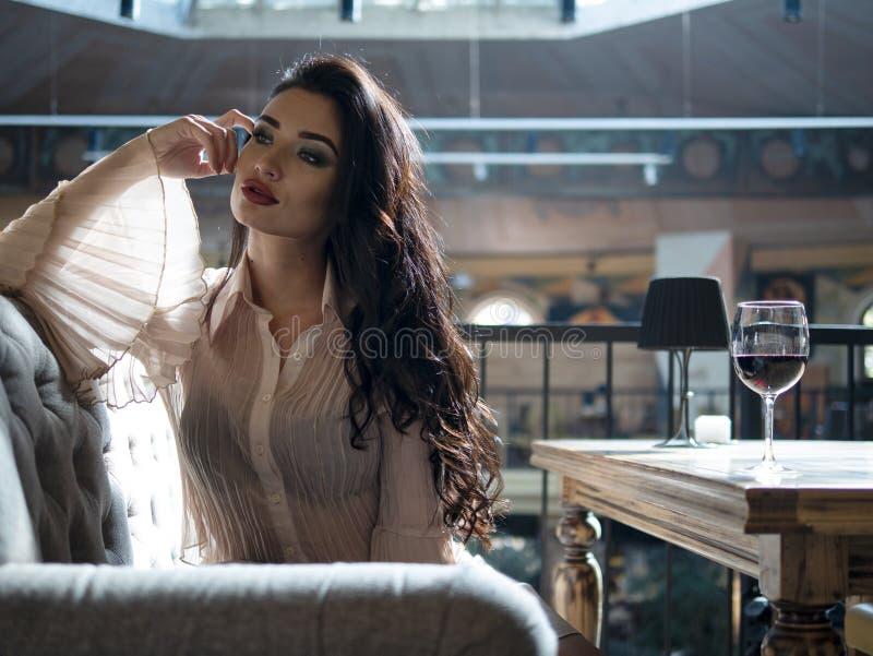 Den attraktiva flickan med ursnyggt hår poserar på kamera med en allvarlig framsida som sitter på soffan fotografering för bildbyråer