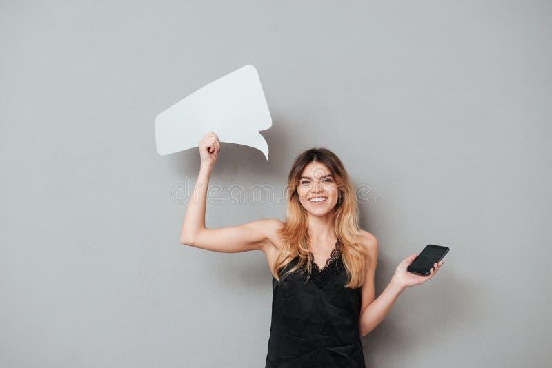 Den attraktiva flickan som rymmer mobiltelefonen för den tomma skärmen, och anförande bubblar arkivfoto