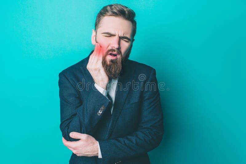 Den attraktiva grabben i följe har ett problem Han har en tand att smärta Det är ruskigt Han lider från det Smärtapunkten är arkivbild