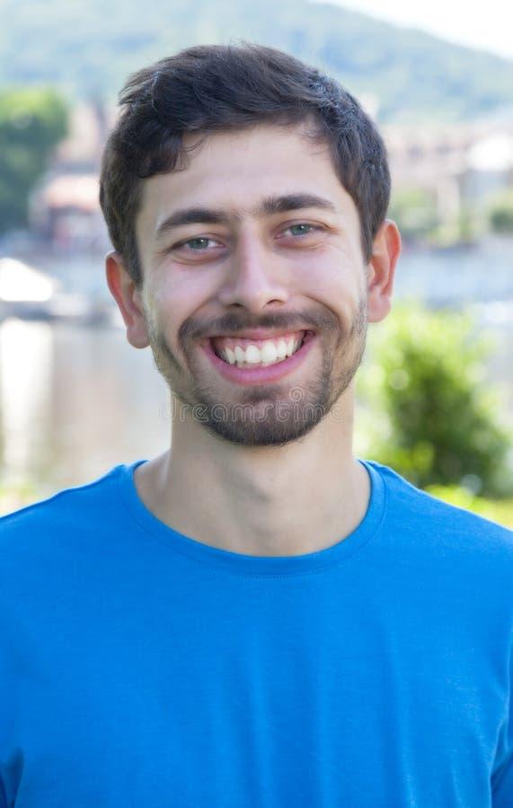 Den attraktiva grabben med skägg- och blåttskjortan är lycklig arkivbild