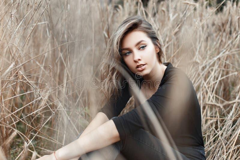 Den attraktiva gulliga lantliga unga kvinnan i stilfull svart t-skjorta i tappningjeans vilar i ett fält med torrt gräs arkivbilder