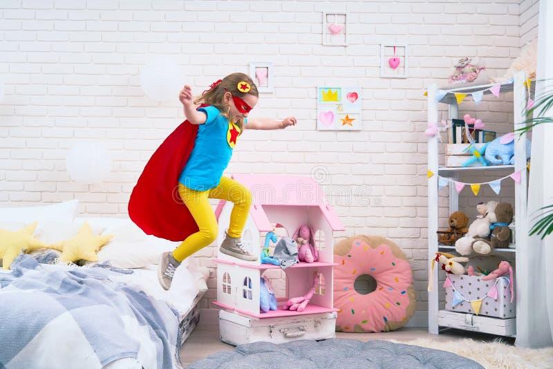 Den attraktiva gulliga lilla flickan hoppar från säng för att flyga, när hon spelar superheroen med kappan och maskeringen hemma  arkivbilder
