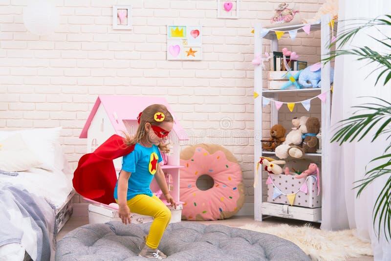 Den attraktiva gulliga lilla flickan hoppar från säng för att flyga, när hon spelar superheroen med kappan och maskeringen hemma  royaltyfri bild