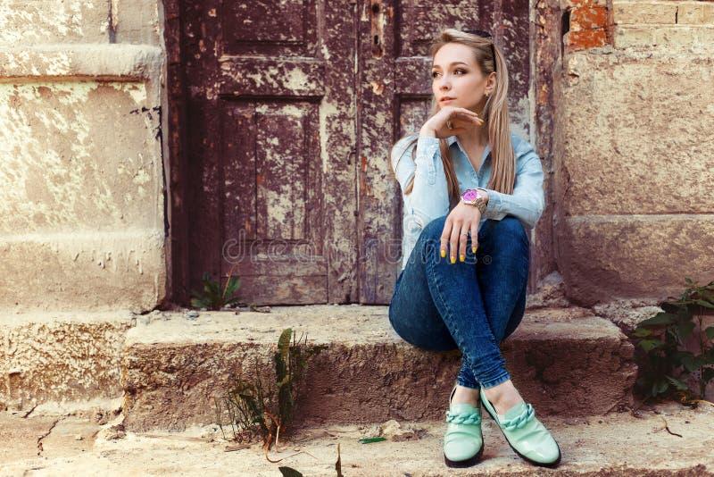 Den attraktiva härliga försiktiga flickan sitter i staden på momenten av den gamla byggnaden i jeans och modeskodon arkivbild