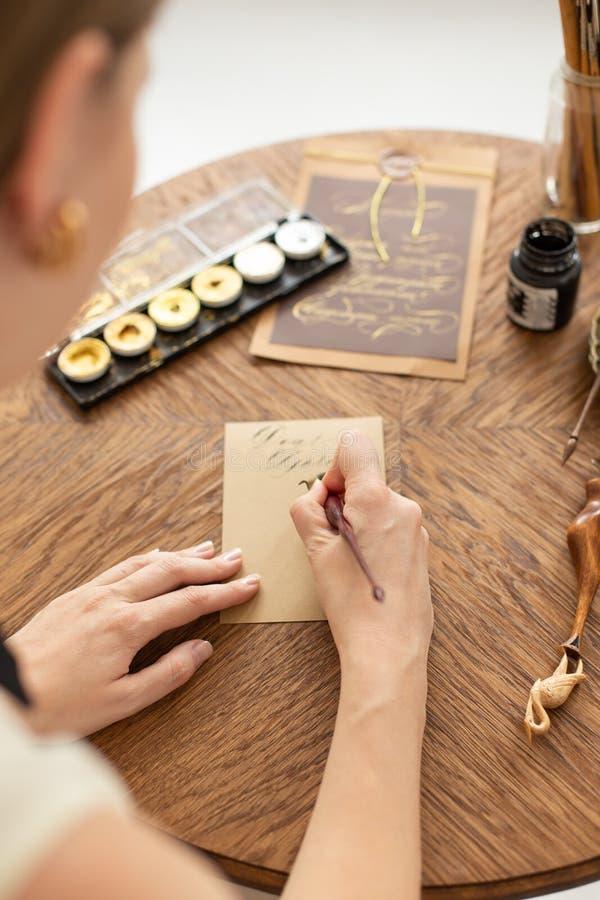 Den attraktiva kvinnakalligrafen rymmer en penna med färgpulver och tecken ett kort i handskriven stilsort N?rbild slapp fokus royaltyfri fotografi