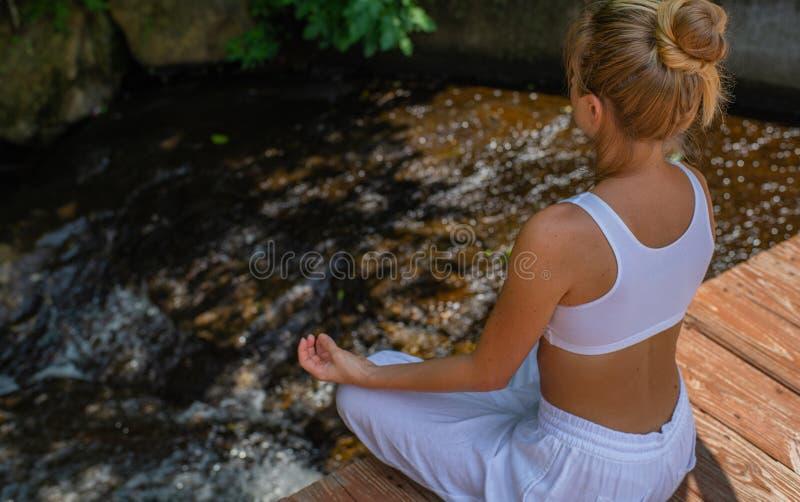 Den attraktiva kvinnan öva yoga, och meditationen som sitter i lotusblomma, poserar nära vattenfallet i morgon arkivfoto