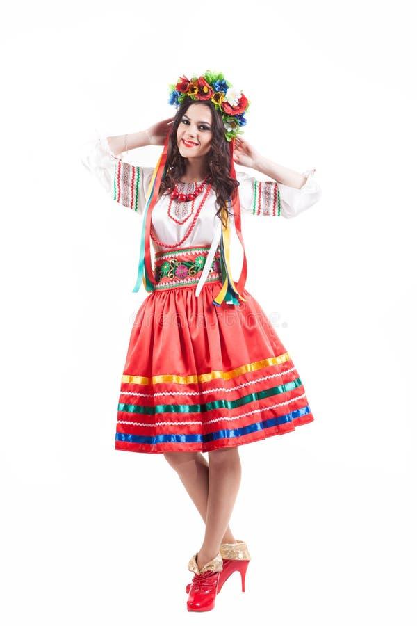 Den attraktiva kvinnan bär den ukrainska nationella klänningen som isoleras på vit bakgrund arkivfoton