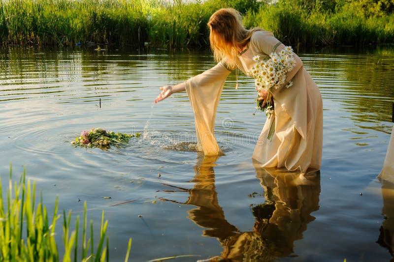 Den attraktiva kvinnan fäller ned kransen i vatten fotografering för bildbyråer
