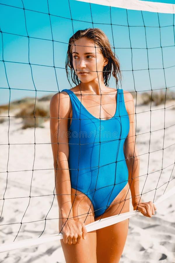 Den attraktiva kvinnan i blå bikini med tennis förtjänar på den sandiga stranden royaltyfri bild
