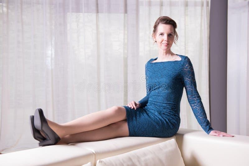 Den attraktiva kvinnan i blått klär sammanträde på soffan royaltyfri bild