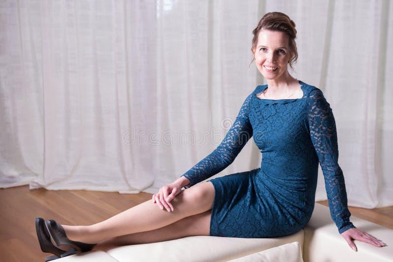 Den attraktiva kvinnan i blått klär sammanträde på soffan royaltyfri foto