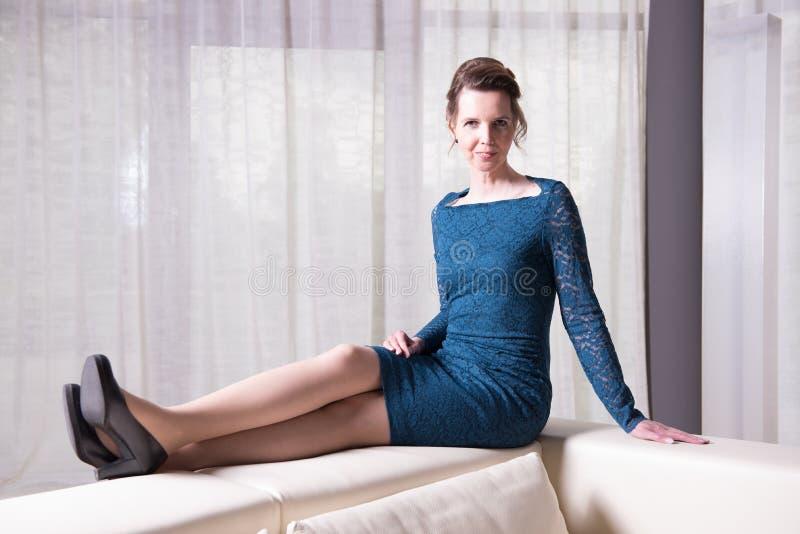 Den attraktiva kvinnan i blått klär sammanträde på soffan arkivfoto
