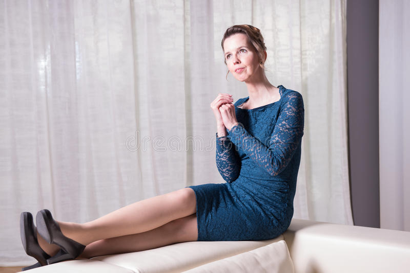 Den attraktiva kvinnan i blått klär sammanträde på soffan arkivfoton