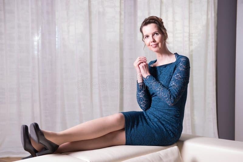 Den attraktiva kvinnan i blått klär sammanträde på soffan fotografering för bildbyråer
