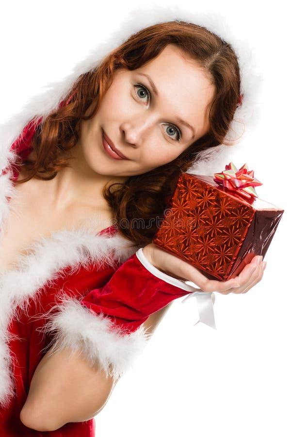 Den attraktiva kvinnan i jul klär handen en present royaltyfria bilder