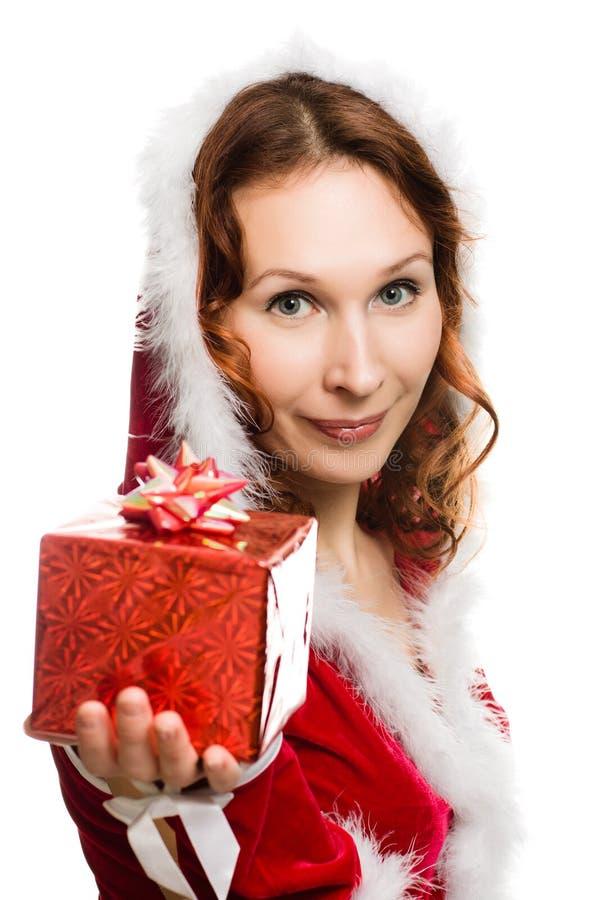 Den attraktiva kvinnan i jul klär handen en present fotografering för bildbyråer