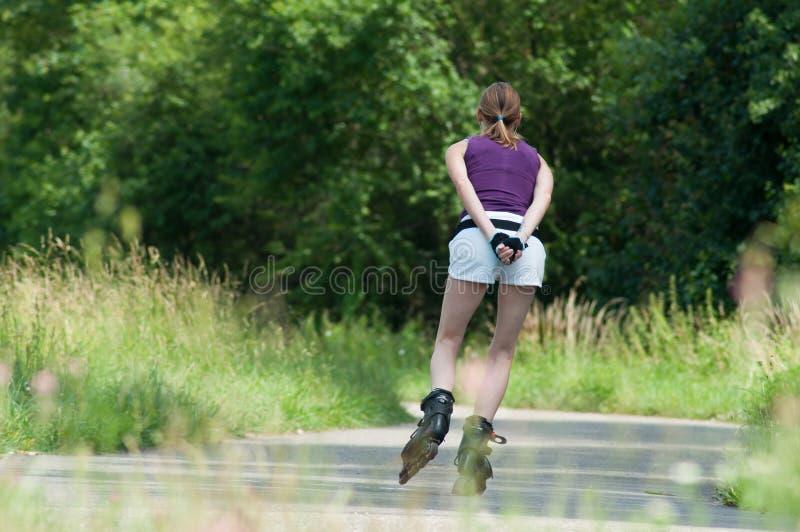 Den attraktiva kvinnan i kortslutningar kör rullskridskor i gränsskog royaltyfri bild