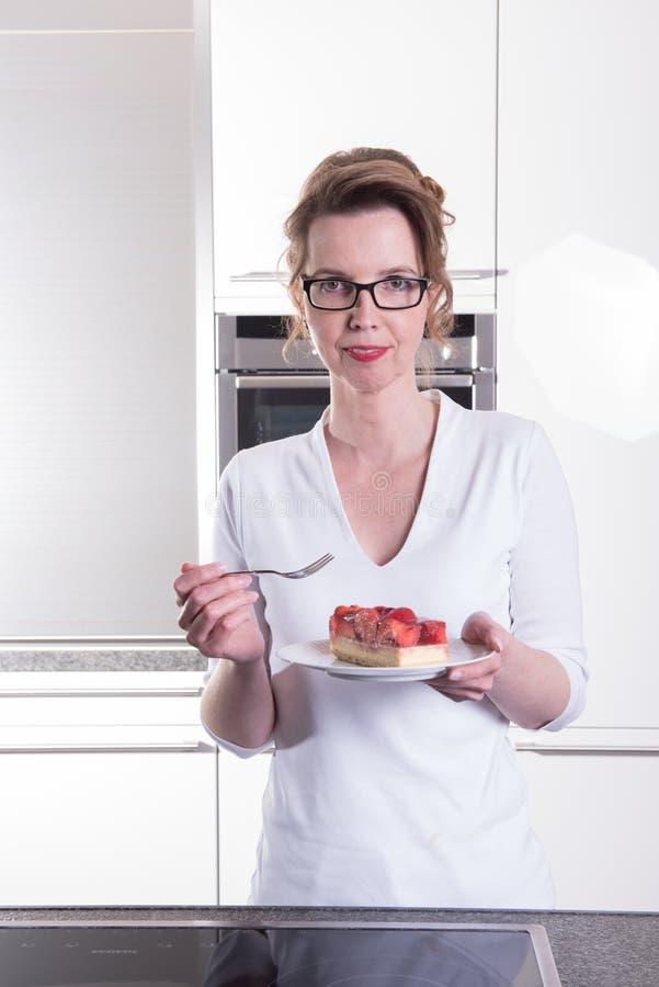 Den attraktiva kvinnan i modernt ktchen äta jordgubbekakan fotografering för bildbyråer