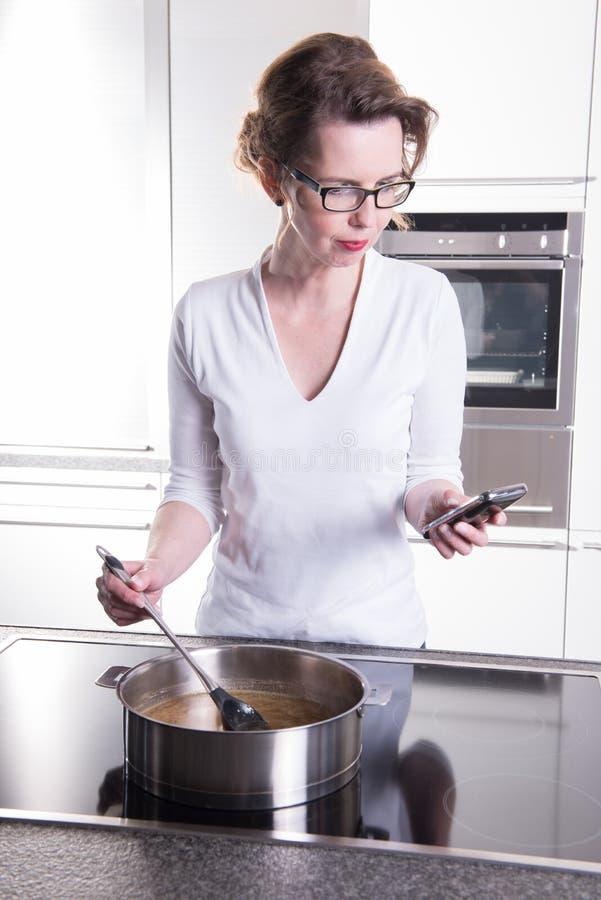 Den attraktiva kvinnan i modernt ktchen matlagning och att se på phoen arkivfoto