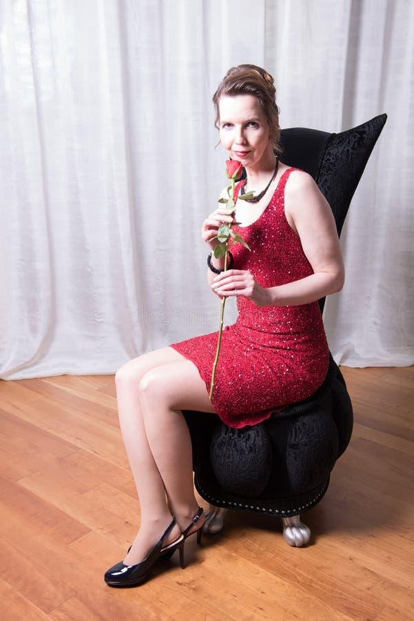 Den attraktiva kvinnan i röd klänning med steg royaltyfria foton