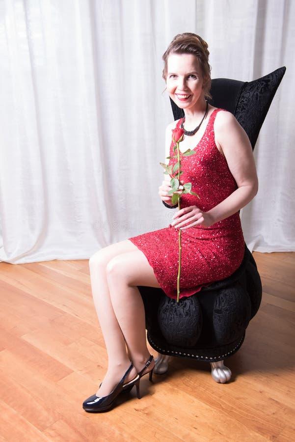 Den attraktiva kvinnan i röd klänning med steg royaltyfri bild