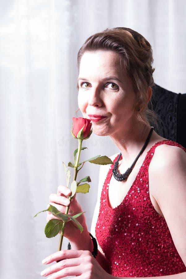 Den attraktiva kvinnan i röd klänning med steg arkivfoton