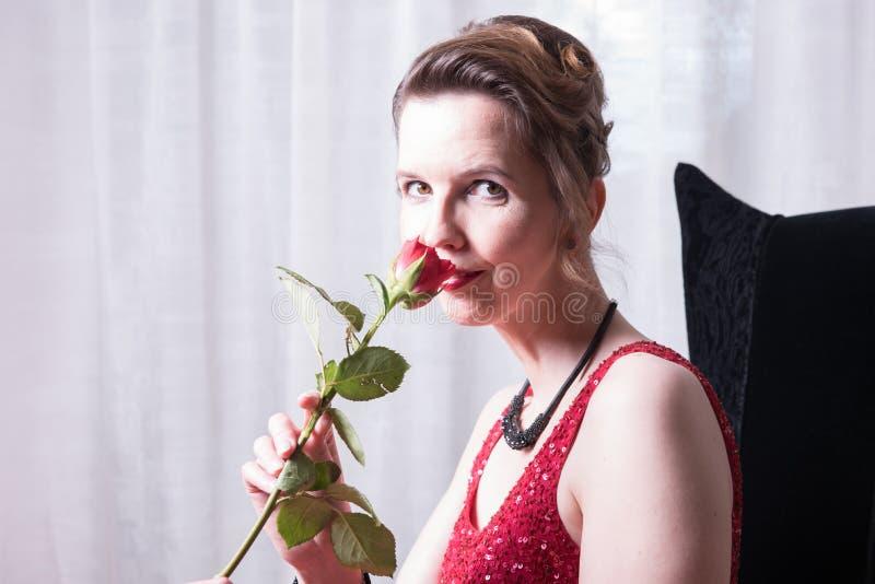 Den attraktiva kvinnan i röd klänning med steg arkivbild