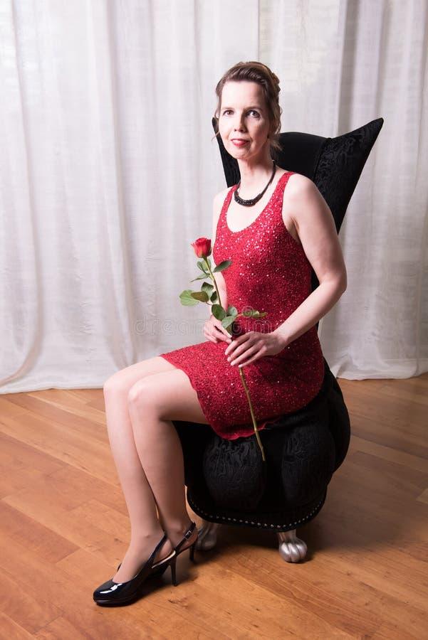 Den attraktiva kvinnan i röd klänning med steg royaltyfri fotografi