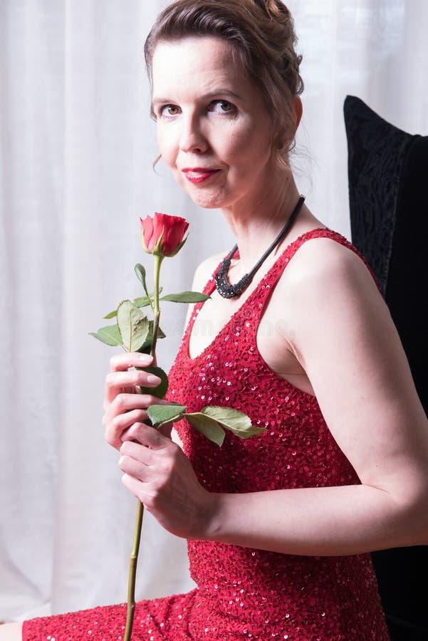 Den attraktiva kvinnan i röd klänning med steg royaltyfri foto