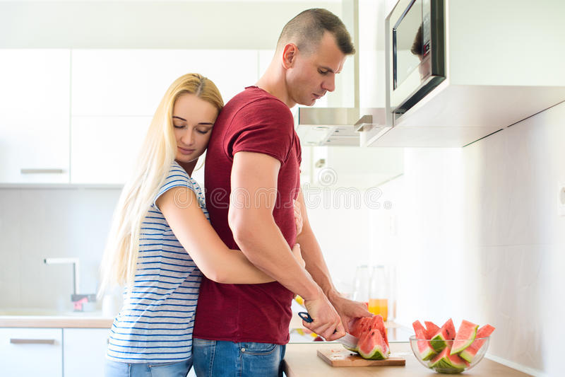 den attraktiva kvinnan kramar hennes make, medan han klipper den röda vattenmelon i deras stora moderna vita kök arkivfoto