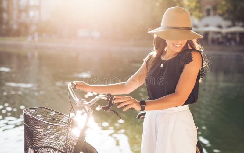 Den attraktiva kvinnan med cykeln på parkerar arkivbilder