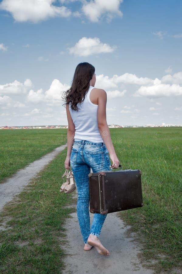 Den attraktiva kvinnan med den gamla resväskan går avlägsen arkivfoton