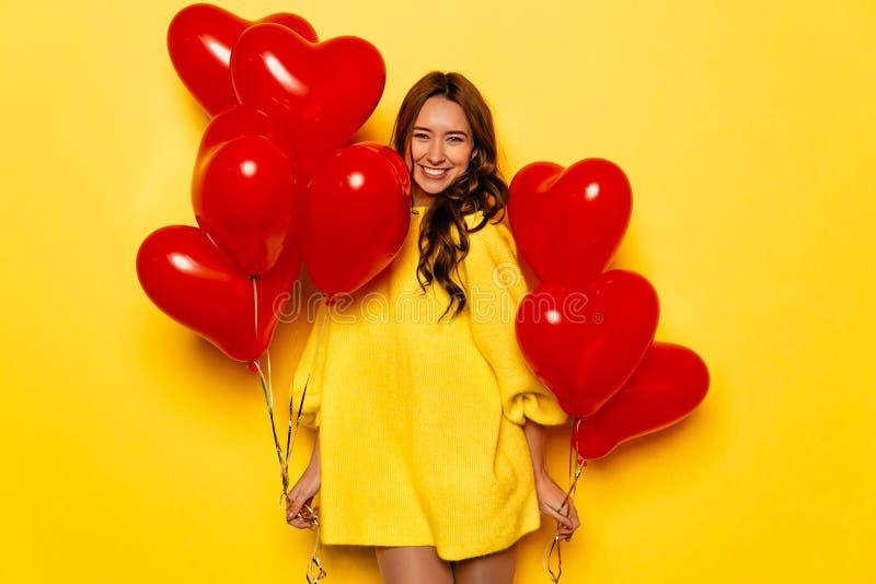 Den attraktiva kvinnan med hjärta formade luftballonger som firar dag för valentin` s royaltyfri foto