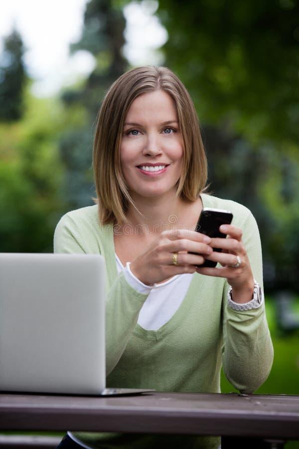 Den attraktiva kvinnan parkerar in med den smarta telefonen arkivfoton