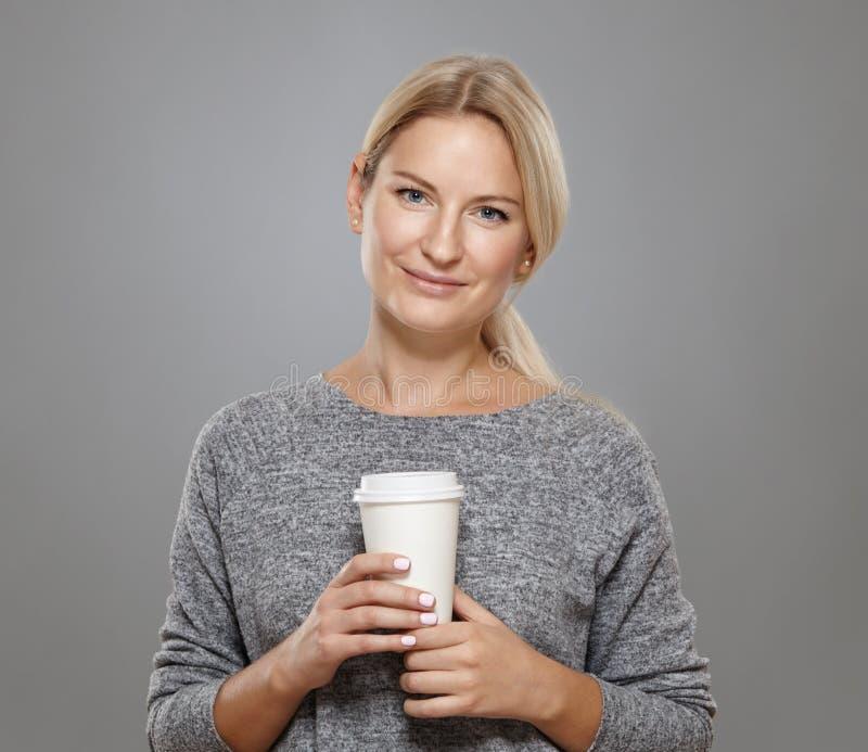 Den attraktiva kvinnan rymmer ett koppkaffe arkivbild