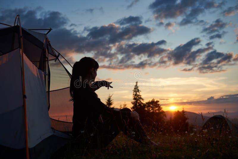 Den attraktiva kvinnan sitter i profil nära tältet på gräs med vildblommor och visar hennes hand i avstånd arkivbilder