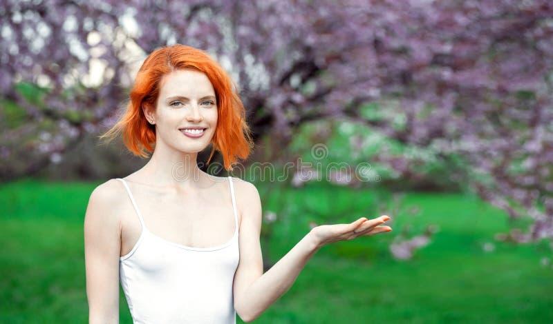 Den attraktiva kvinnan som rymmer n?got p? henne, g?mma i handflatan, medan st? in parkera med blommatr?det royaltyfria bilder