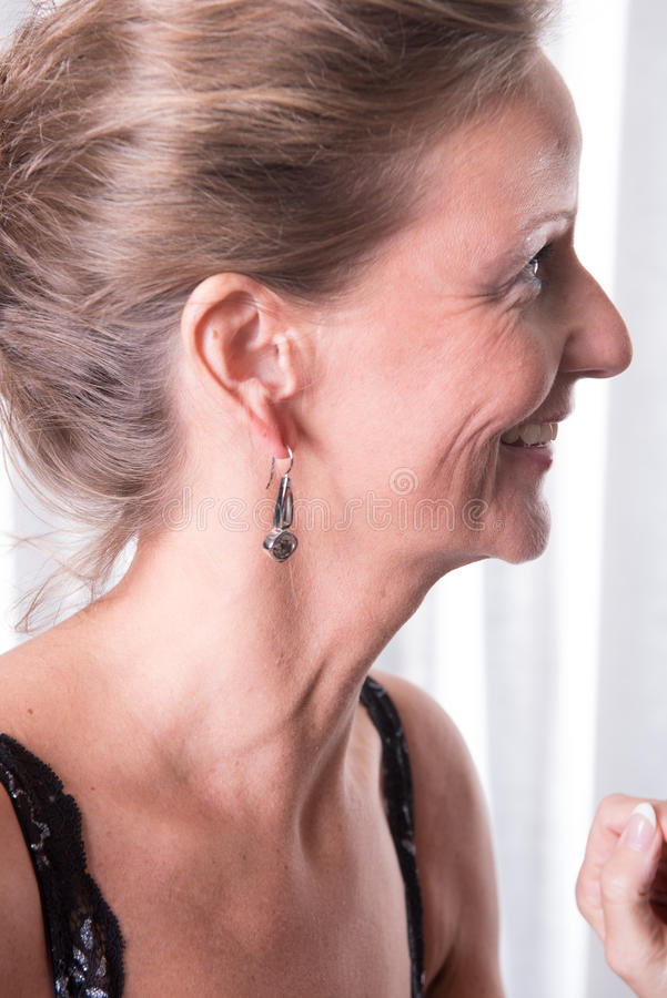 Den attraktiva kvinnan visar hennes örhänge fotografering för bildbyråer