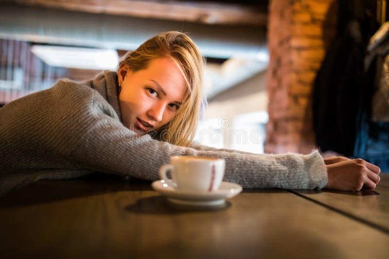 Den attraktiva kvinnliga studenten sitter på kafét med koppen kaffe, önskar att ha att vila, tröttas och evakuerat Dreamful kvinn royaltyfria foton