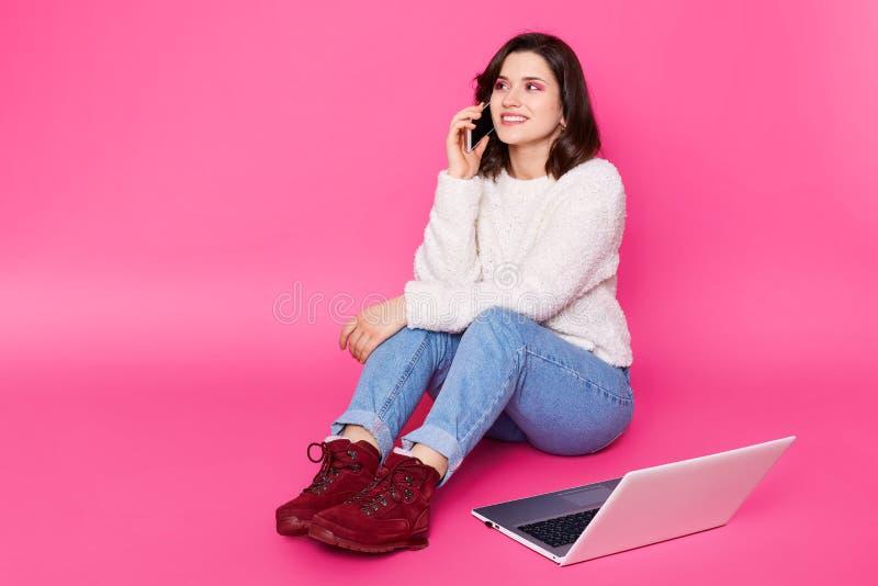 Den attraktiva kvinnlign med härligt leende sitter på golv hemma, talar på mobiltelefonen Den härliga flickan arbetar direktanslu royaltyfri foto