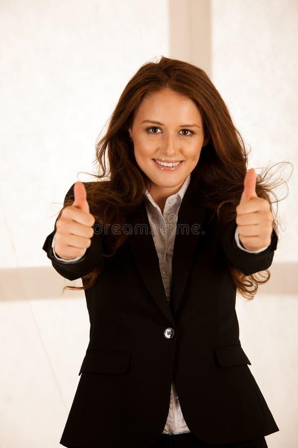 Den attraktiva lyckade affärskvinnan visar upp tumb som en gest f royaltyfri fotografi