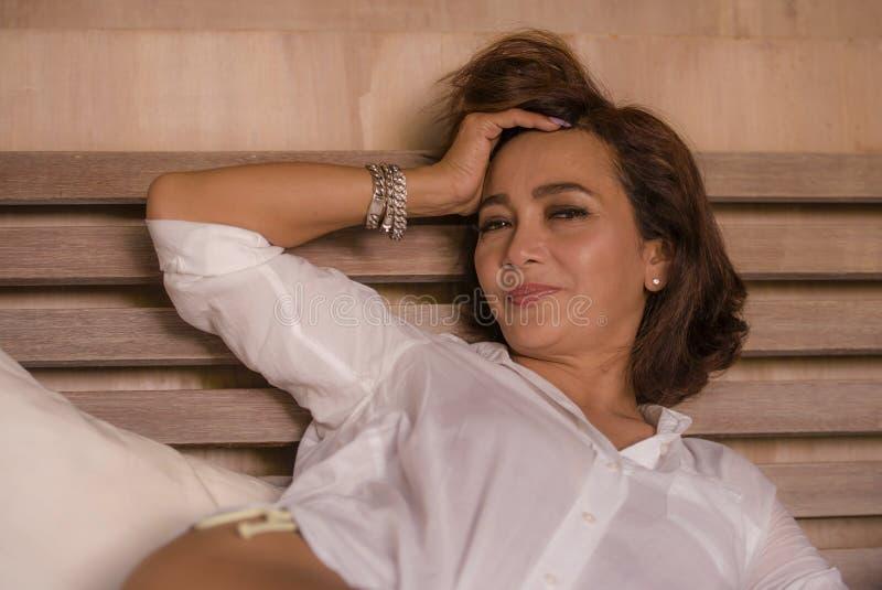 Den attraktiva lyckliga och sexiga mogna kvinnan åldrades 50-tal till 60-tal som ler det gladlynta och charmiga hemmastadda sovru arkivfoto