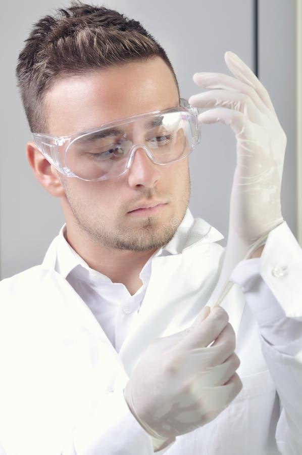 Den attraktiva manliga medicinska arbetaren sätter på rubber handskar arkivfoton