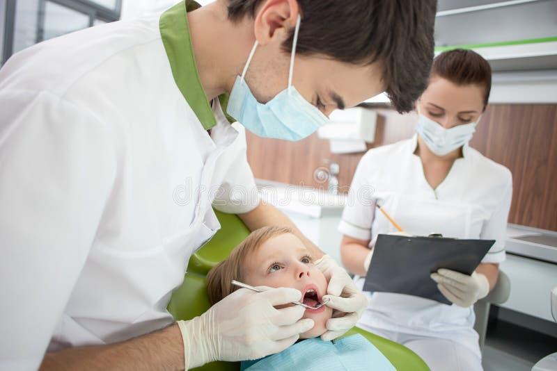 Den attraktiva manliga tandläkaren analyserar mänsklig hälsa royaltyfria foton